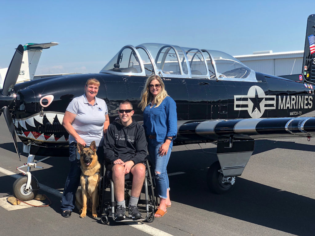 K9 Bear and veteran with family in front of world war II fighter plane